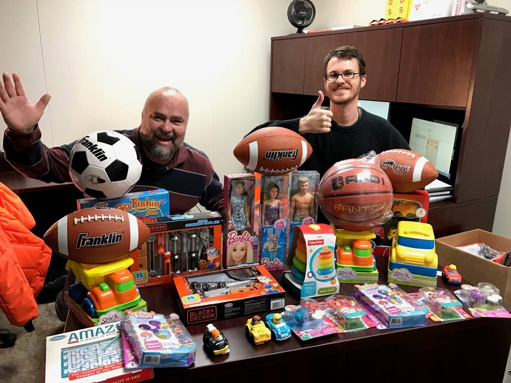 Russell Martinez and David Kaylor having fun with part of FreshPoint Dallas' toy donation to The Family Place.