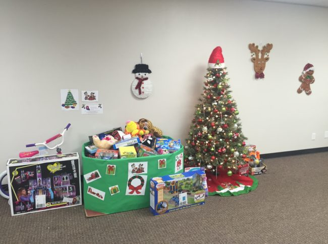 Dozens of holiday toys around the tree FreshPoint Dallas ready to donate to The Family Place.